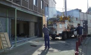 Deux ouvriers de Solumetal posent une vitre à l'aide d'une grue.